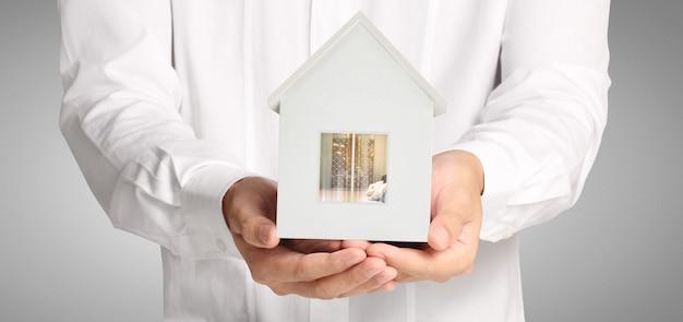 Estructura residencial de la casa en una mano, idea de hogar de negocios