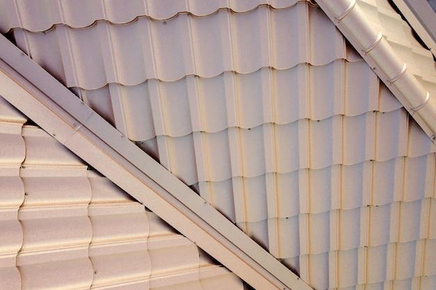 Estructura del techo de la casa cubierta con láminas de tejas de metal marrón.