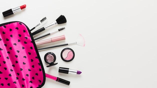 Estuche de maquillaje rosa con cosméticos y pinceles.