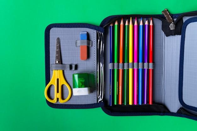 Estuche con útiles escolares sobre un fondo de papel verde con espacio de copia. lay flat