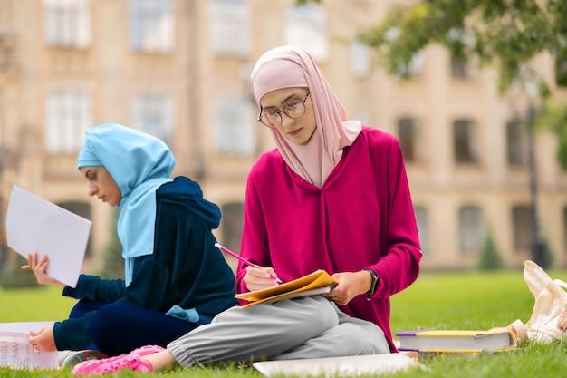 Estudiando duro. estudiante musulmán con gafas y hijab rosa estudiando duro cerca de un amigo