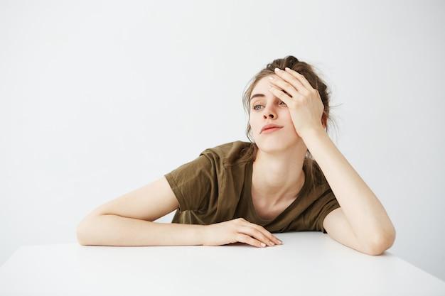 Estudiante aburrido aburrido cansado de la mujer joven con el bollo que se sienta en la tabla sobre el fondo blanco.