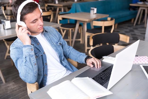 Estudiante adolescente en auriculares sentado con el cuaderno en la mesa