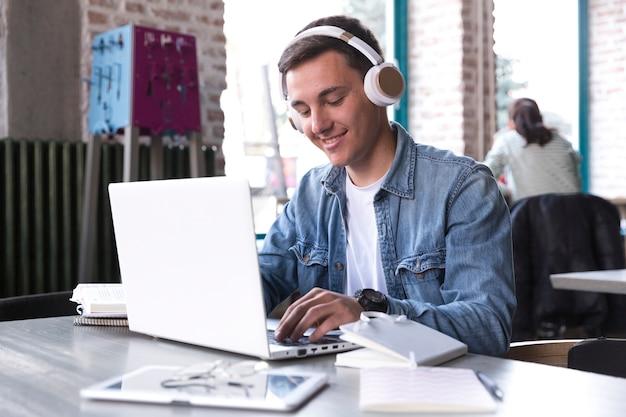Estudiante adolescente en auriculares sentado en la mesa y escribiendo en el cuaderno