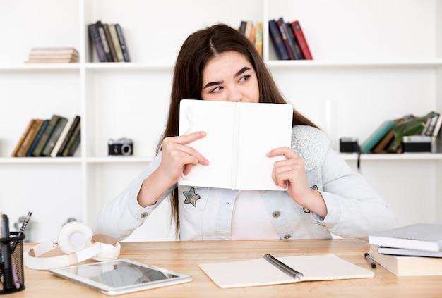 Estudiante adolescente con libro abierto en la cara sentado en la mesa