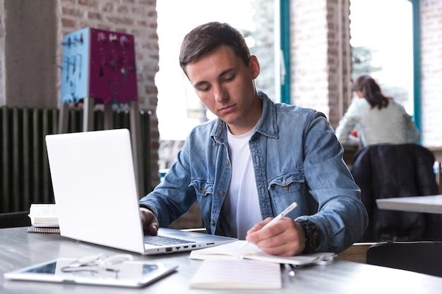 Estudiante adolescente sentado a la mesa con cuaderno y escribiendo