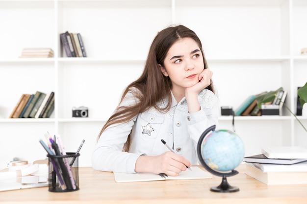 Estudiante adolescente sentado a la mesa y cuidadosamente escribiendo