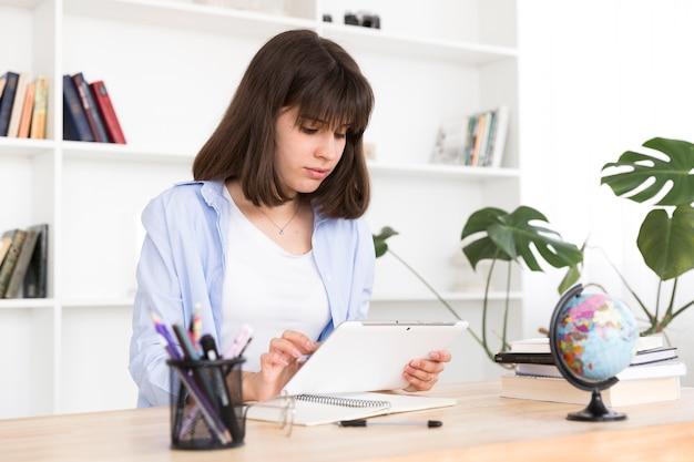 Estudiante adolescente sentado en la mesa y estudiando con tableta