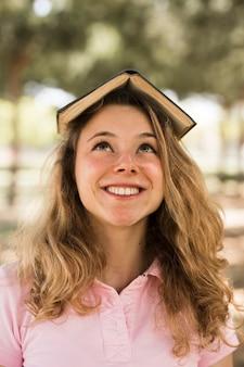 Estudiante adolescente sonriendo con un libro en la cabeza
