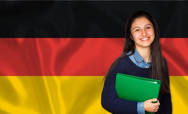 Estudiante adolescente sonriendo sobre bandera alemana