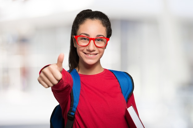 Estudiante adolescente sonriente sosteniendo un libro