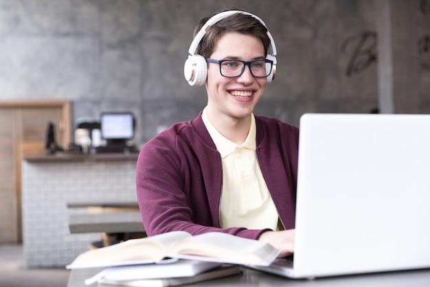 Estudiante adolescente en los vidrios y los auriculares que se sientan con el cuaderno en la tabla en sala de clase