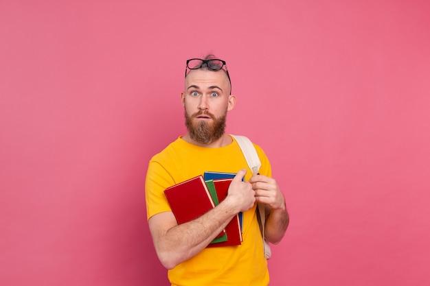 Estudiante adulto alegre chico de ropa casual con barba y mochila sosteniendo libros aislados en rosa