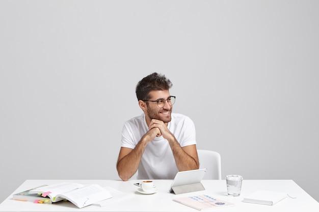 Estudiante sin afeitar hipster de moda tiene peinado de moda sentado en el lugar de trabajo