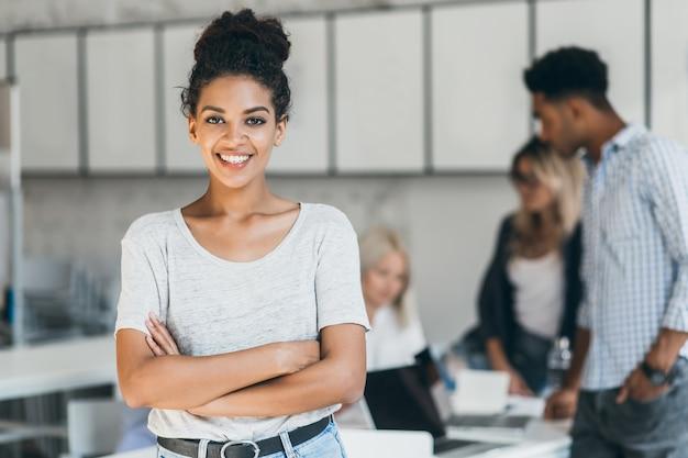 Estudiante africana entusiasta disfrutando de la compañía con amigos en la sala de conferencias. retrato interior del oficinista negro sonriente posando con los brazos cruzados delante de colegas extranjeros.