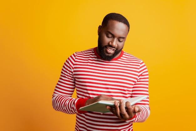 Estudiante africano atractivo leer libro disfrutar de páginas de mirada de hobby en pared amarilla