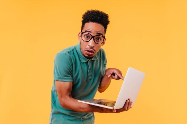 Estudiante africano decepcionado que presenta con la computadora portátil. freelancer masculino negro sorprendido sosteniendo la computadora.