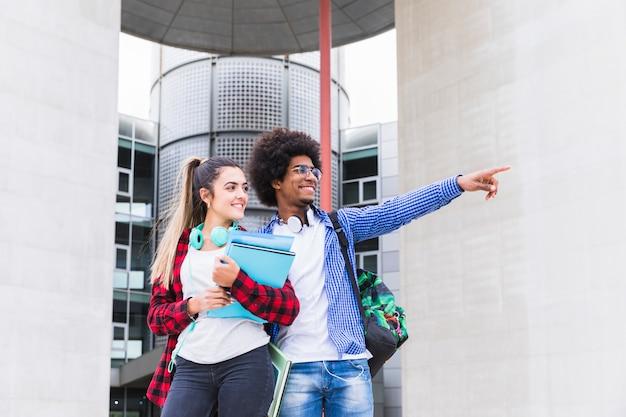 Un estudiante africano de pie junto a la universidad mostrando algo a su amiga.