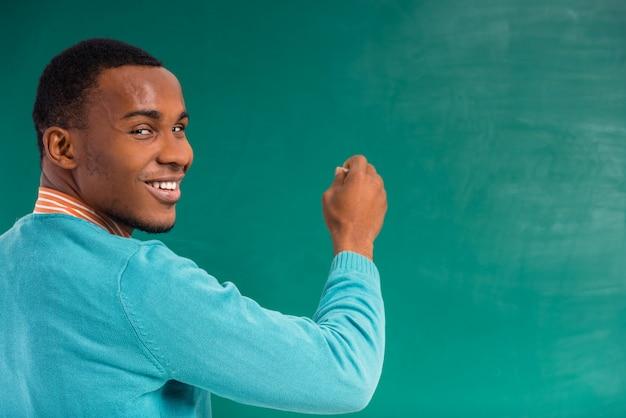 Estudiante africano en una pizarra verde.