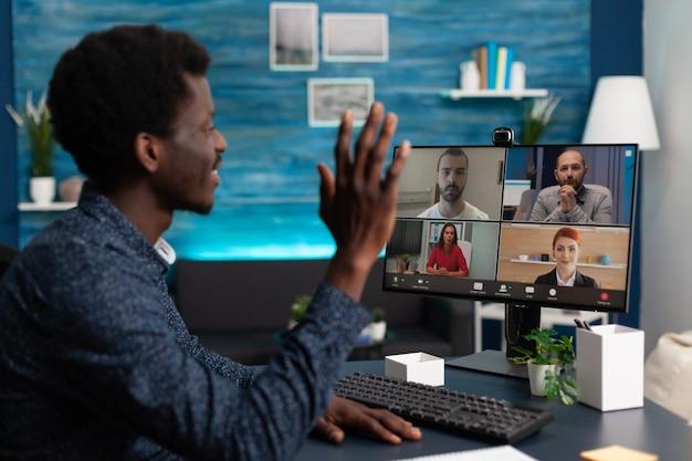 Estudiante africano saludando al equipo universitario en videollamada