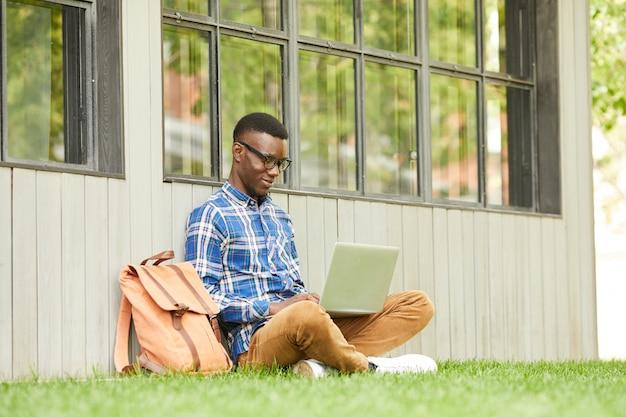 Estudiante africano usando laptop al aire libre