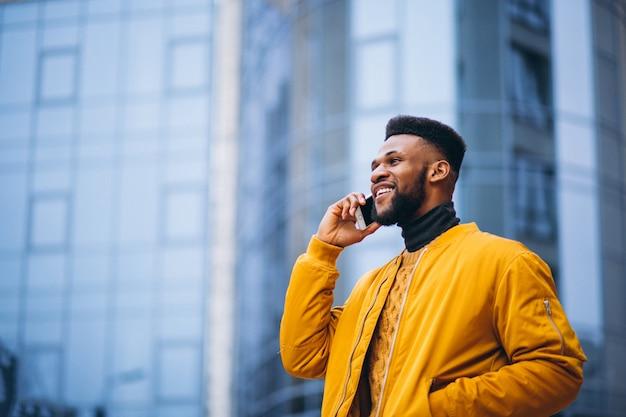 Estudiante afroamericano caminando en la calle y hablando por teléfono
