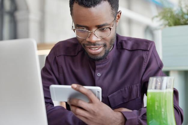 El estudiante afroamericano concentrado y encantado mira películas o videos en un teléfono inteligente, usa ropa formal y gafas redondas