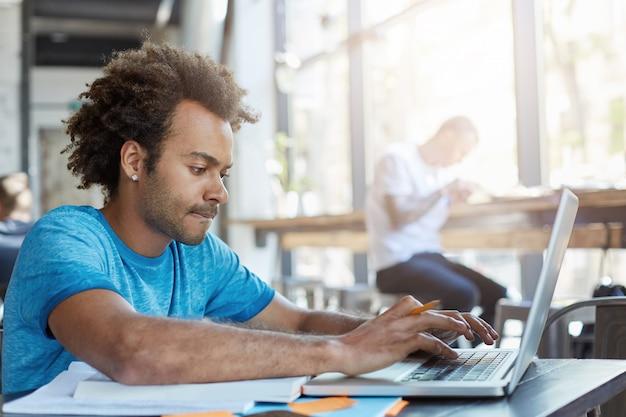 Estudiante afroamericano elegante mecanografía en la computadora portátil mientras está sentado en la mesa de café con libros de texto, trabajando en la tarea, habiendo enfocado mirada concentrada. personas, tecnología moderna y educación