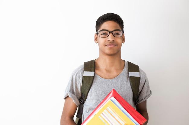 Estudiante afroamericano feliz en copas con libros.