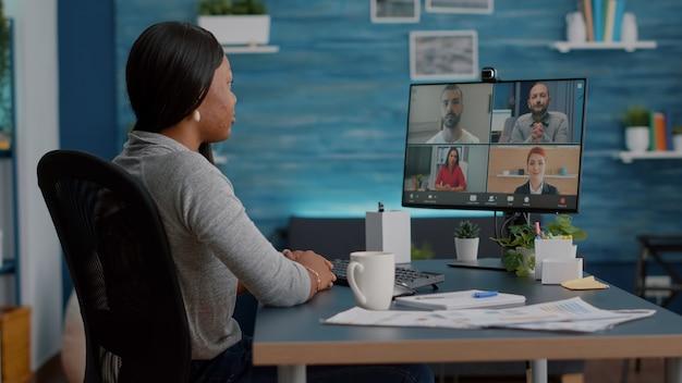 Estudiante afroamericano hablando con el equipo de la universidad discutiendo ideas de marketing durante el seminario web en línea