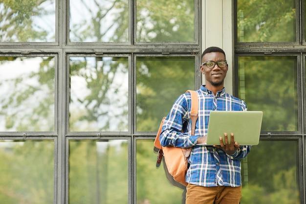Estudiante afroamericano posando con laptop al aire libre
