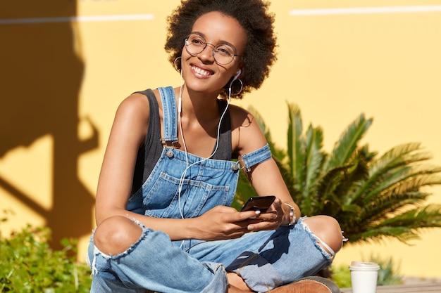 Una estudiante alegre escucha un audiolibro en auriculares, tiene cursos en línea, disfruta pasar tiempo en un lugar tropical, mantiene las piernas cruzadas, usa un mono casual de mezclilla, se concentra a un lado con una sonrisa agradable