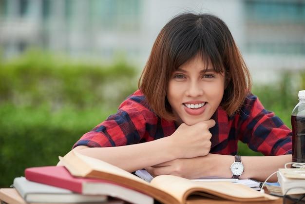 Estudiante alegre mirando a la cámara haciendo hometask en el jardín del campus