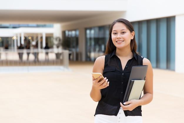 Estudiante alegre que sostiene los cuadernos