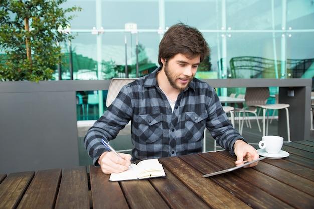 Estudiante alegre tomando apuntes para ensayo.