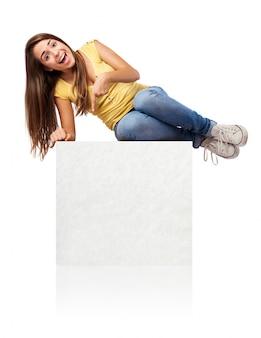 Estudiante alegre tumbada sobre un cartel vacío