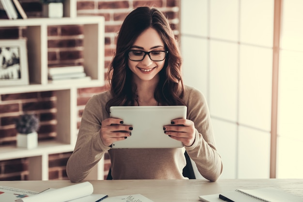 Estudiante en anteojos está utilizando una tableta digital.