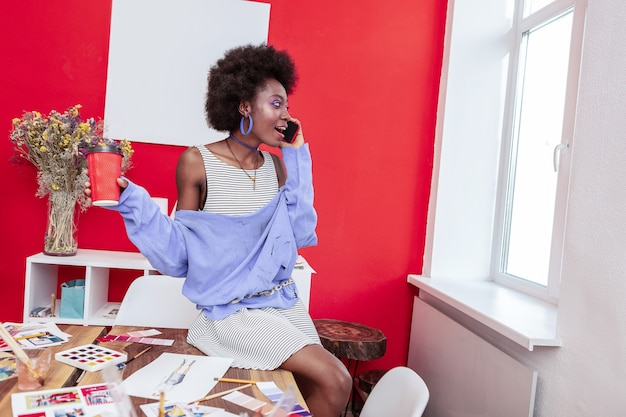 Estudiante de arte. estudiante de arte creativo inteligente hablando con su novio por teléfono mientras toma café