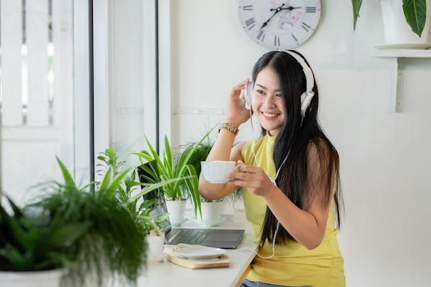 Estudiante asiática sonriente usa auriculares inalámbricos estudia en línea con skype teacher en una cafetería, educación, nueva normalidad