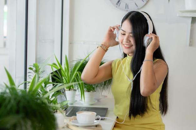 Una estudiante asiática sonriente usa auriculares inalámbricos para estudiar en línea con un maestro de skype en una cafetería,