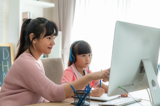 Estudiante asiática con videoconferencia de madre e-learning con profesor en la computadora en la sala de estar