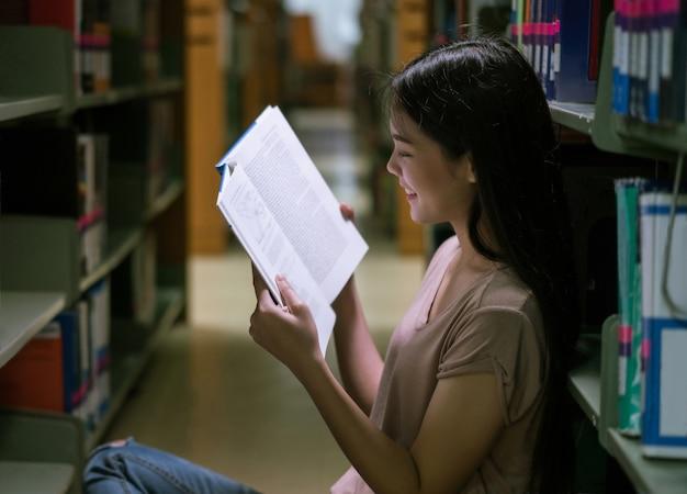 Estudiante asiático en la biblioteca en la estantería. ella está leyendo