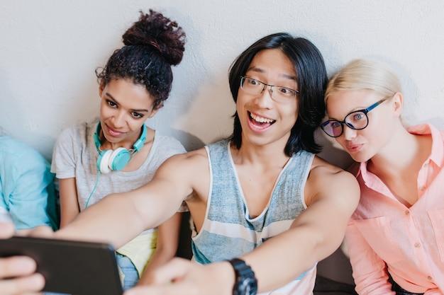 Estudiante asiático emocionado en gafas tomando una foto de sí mismo sentado entre una mujer rubia y una joven africana. amigos con estilo haciendo selfie después de la prueba en la universidad.