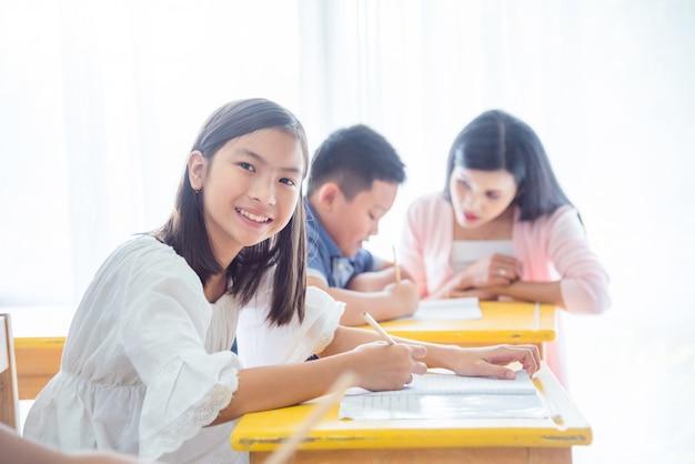 Estudiante asiático feliz de la escuela primaria que estudia en sala de clase y que sonríe en la cámara.