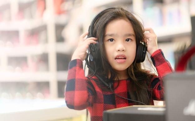 Estudiante asiático feliz de la muchacha que escucha la música con los auriculares