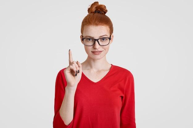 Estudiante astuto pecosa inteligente tiene una idea brillante en mente, levanta el dedo índice en gesto de eureka