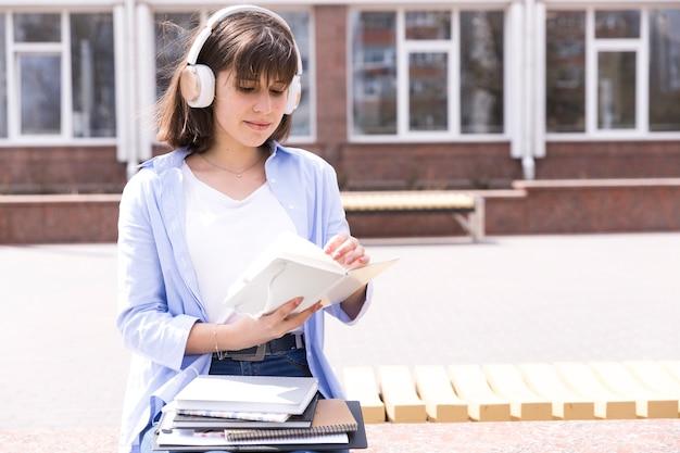Estudiante en auriculares leyendo notas.