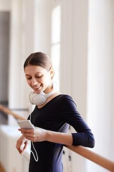 Estudiante de ballet con smartphone en estudio