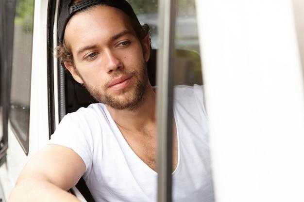 Estudiante barbudo en snapback conduciendo un jeep blanco, sacando la cabeza y el codo de la ventana abierta, mirando hacia el camino mientras se detiene en el cruce para la luz roja