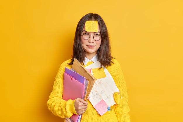 Una estudiante bastante asiática con papel adhesivo recordatorio en la frente lleva carpetas con papeles y se prepara para una prueba difícil, lleva gafas redondas y un jersey.